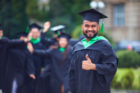 portrait of successful indian student in graduation gown thumb up Stock Photo