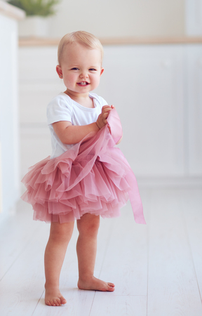 cute little baby girl in tutu skirt stands on the floor at home