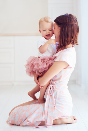 happy mother hugging her little baby girl at home
