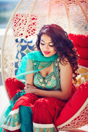 beautiful oriental woman in traditional dress relaxing, dreaming on sofa