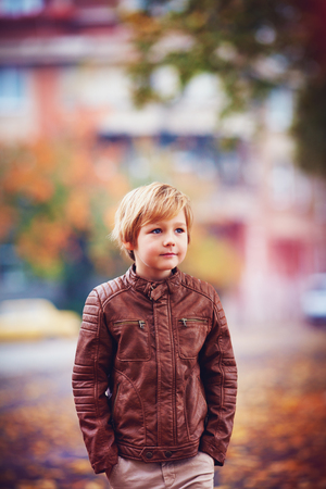 portrait of smiling young boy, kid walking in autumn city park among fallen leaves