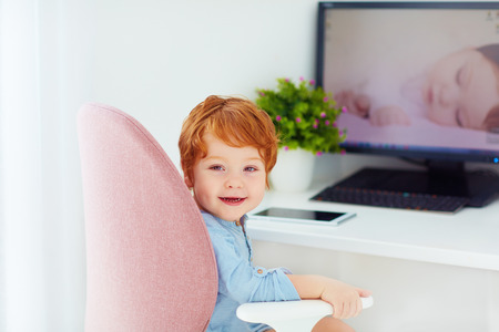happy redhead toddler baby boy is sitting in office chair at working place