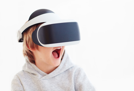 excited young boy, kid wearing virtual reality goggles, playing videogames