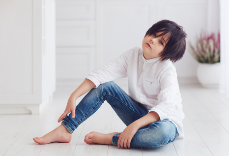 young calm boy,  sitting barefoot on the floor
