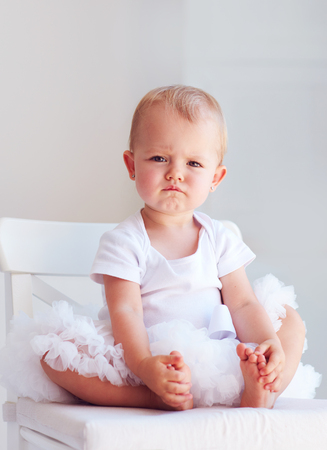 portrait of one year old baby girl with serious face expression and fiery temper posing on the chair