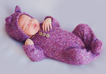 cute newborn baby girl in purple knitted overall is sleeping peacefully Stock Photo - 113965589