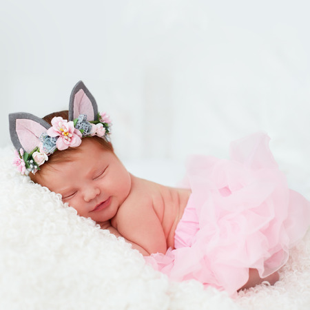 beautiful, one week old newborn baby girl smiling, in pink tutu skirt and floral head band