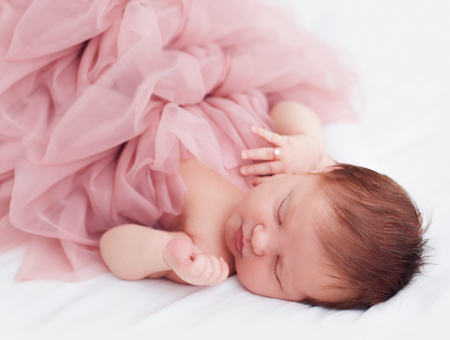 newborn, two weeks old baby girl in ruffle dress and with finger ring is sleeping peacefully