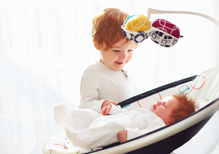 happy toddler baby brother welcoming his little baby sister, that lying in cradle swings Archivio Fotografico