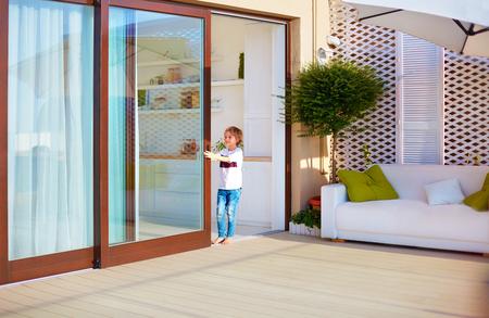 Niño feliz, niño abriendo la puerta corrediza en el patio de la azotea en casa Foto de archivo