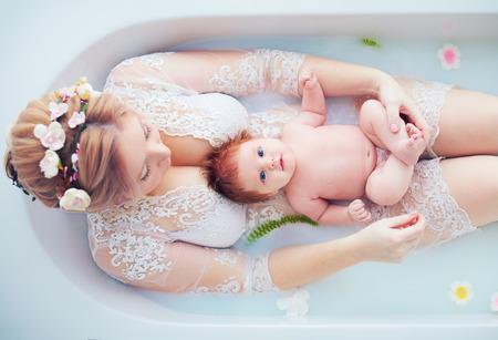 jeune mère heureuse avec une petite fille nouveau-née, fille dans un bain de lait floral