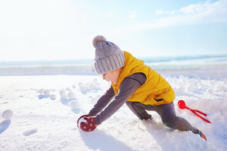 happy baby boy playing snowballs at sunny winter day Stock Photo