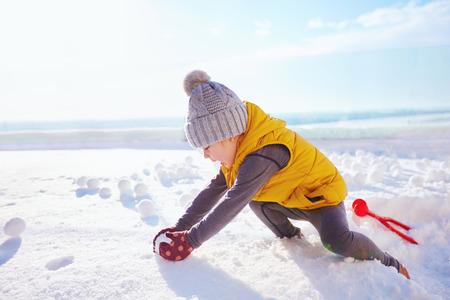 happy baby boy playing snowballs at sunny winter day 免版税图像