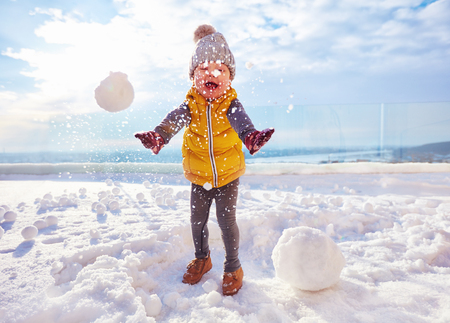 happy baby boy playing snowballs at sunny winter day Stok Fotoğraf