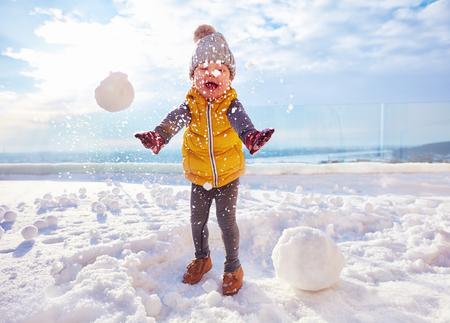 heureux petit garçon jouant aux boules de neige au jour d'hiver ensoleillé