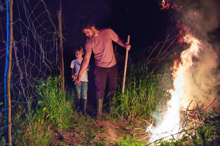 father and son, villagers burning brushwood on fire at night, seasonal cleaning of the countryside area, village lifestyle