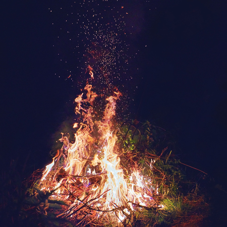 burning brushwood on fire at night, seasonal cleaning of the countryside area, spurts of flame rising up in the air