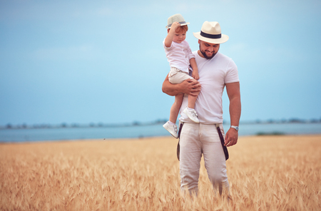 happy father with toddler son walking through the ripe wheat field