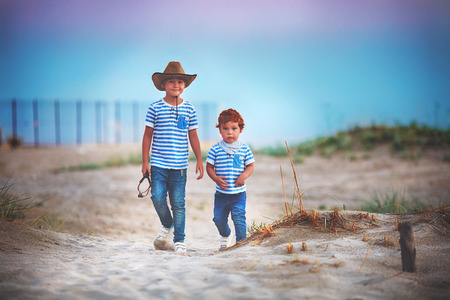 two cute brothers, friends walking through the sandy desert field, playing cowboys, summer adventure