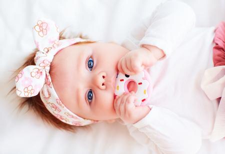 simpatica neonata rosicchia un massaggiagengive in silicone