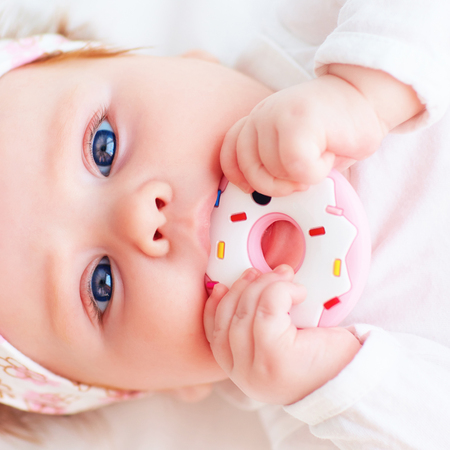 cute little baby girl nibble a silicone doughnut teether