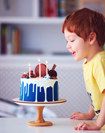 cute redhead happy boy, kid blowing candles on birthday cake at his third birthday