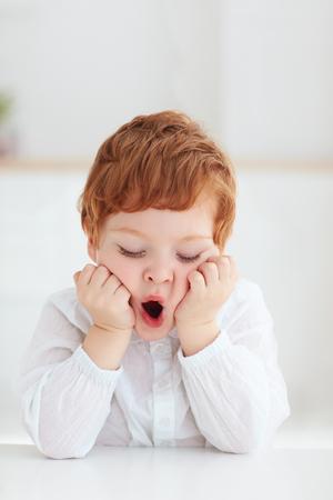 Portrait d'enfant d'âge préscolaire ennuyé mignon, bébé garçon bâillant assis à la table Banque d'images
