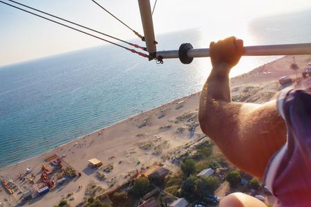 deltaplane planant dans le ciel du coucher du soleil, au-dessus de la côte de la plage d'été Banque d'images