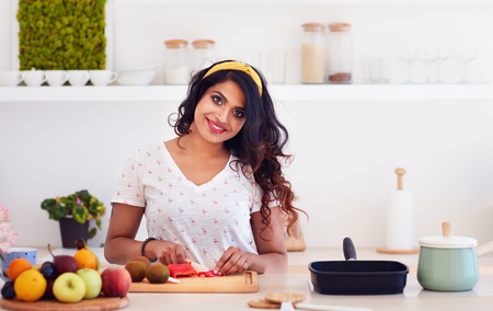 beautiful happy young indian woman cutting vegetables on the kitchen, healthy eating
