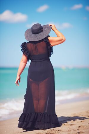 beautiful plus size adult woman enjoys summer vacation by walking along the sandy beach