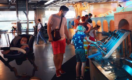 WARSAW, POLAND - June 20, 2019: Family, father with kids testing water pump models in the Copernicus Science Centre in Warsaw, Poland Sajtókép