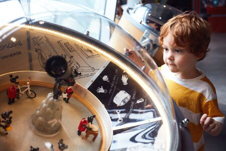 WARSAW, POLAND - June 20, 2019: Kid testing the universe globe model in the Copernicus Science Centre in Warsaw, Poland