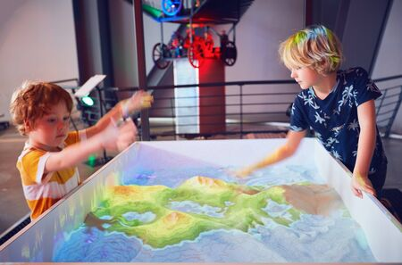 WARSAW, POLAND - June 20, 2019: Kids exploring the color grade differnces according to the terrain elevation that is used in geodesy and map depicting. The Copernicus Science Centre in Warsaw, Poland
