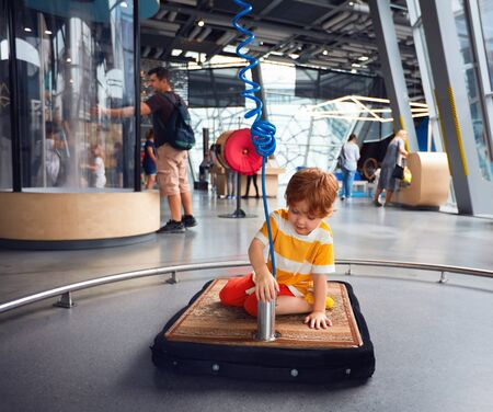 WARSAW, POLAND - June 20, 2019: Curious kid exploring the floating features of rug in combination with the air pump at the Copernicus Science Centre in Warsaw, Poland