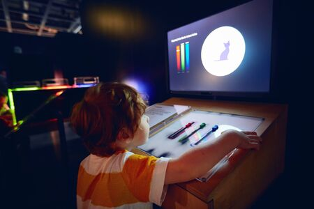 WARSAW, POLAND - June 20, 2019: Curious kid exploring the characteristics of light in the Copernicus Science Centre in Warsaw, Poland