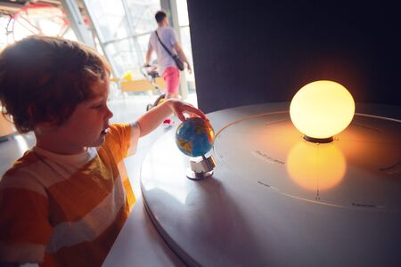 WARSAW, POLAND - June 20, 2019: Kid exploring the season and time of the day changing according to the Earth slope and its position relative to the Sun. The Copernicus Science Centre in Warsaw, Poland