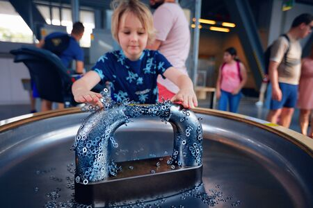 WARSAW, POLAND - June 20, 2019: Kid exploring the feature of magnets and its effection on the metals. The Copernicus Science Centre in Warsaw, Poland Sajtókép