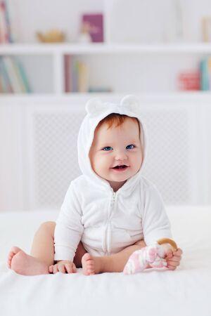 glückliches Säuglingsbaby in lustiger Ohrhaube sitzt zu Hause auf dem Bett