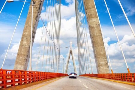 Car is moving through the beautiful bridge. The Francisco del Rosario Sánchez Bridge over the Ozama river in Santo Domingo
