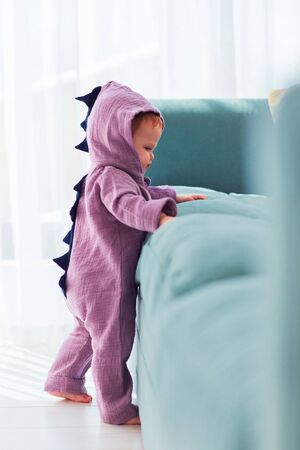adorable infant baby girl in cute dinosaur costume is standing near the sofa Zdjęcie Seryjne