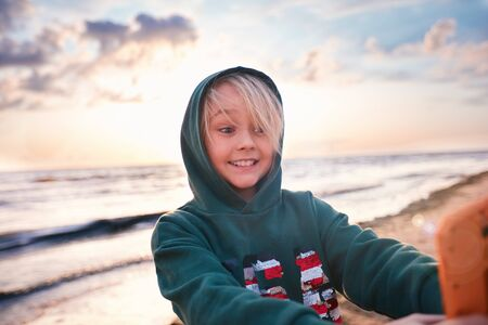 cute happy boy making selfie on the phone at the sunset, on the beach