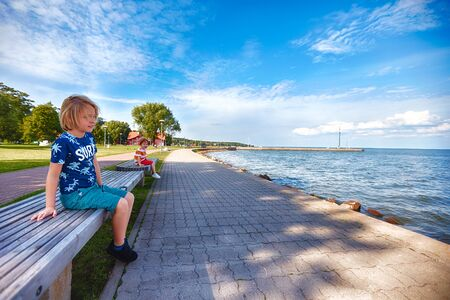 cute kids are sitting on benches at the seaside embankment. Joudkrante, Lithuania
