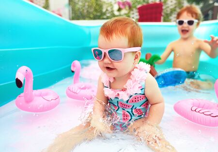 cute happy baby girl having fun in kid pool, summer vacation