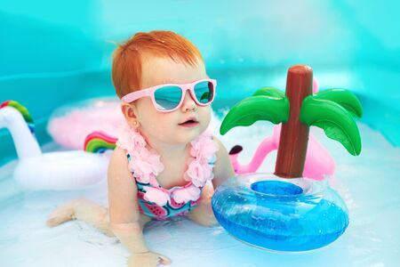cute happy baby girl having fun in kid pool, summer vacation Stock Photo