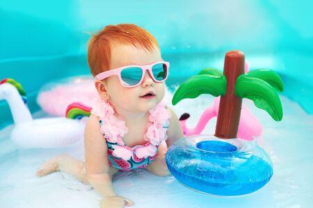 cute happy baby girl having fun in kid pool, summer vacation Foto de archivo