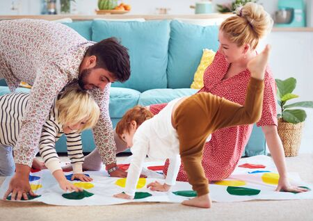 happy family having fun together, playing twister game at home Stock Photo