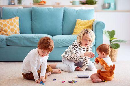 かわいい子供たち、家庭で遊んでいる兄弟、兄は妹に小さなおもちゃの粒子を食べさせない、窒息の危険