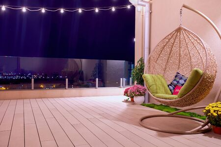 rooftop patio area with hanging swing chair and string lights at night