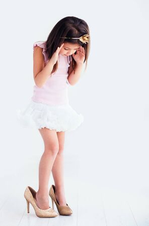 beautiful young girl, kid trying the high heel shoes on