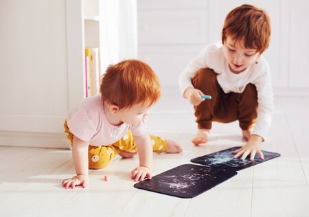 cute redhead siblings having fun, drawing on chalk board at home